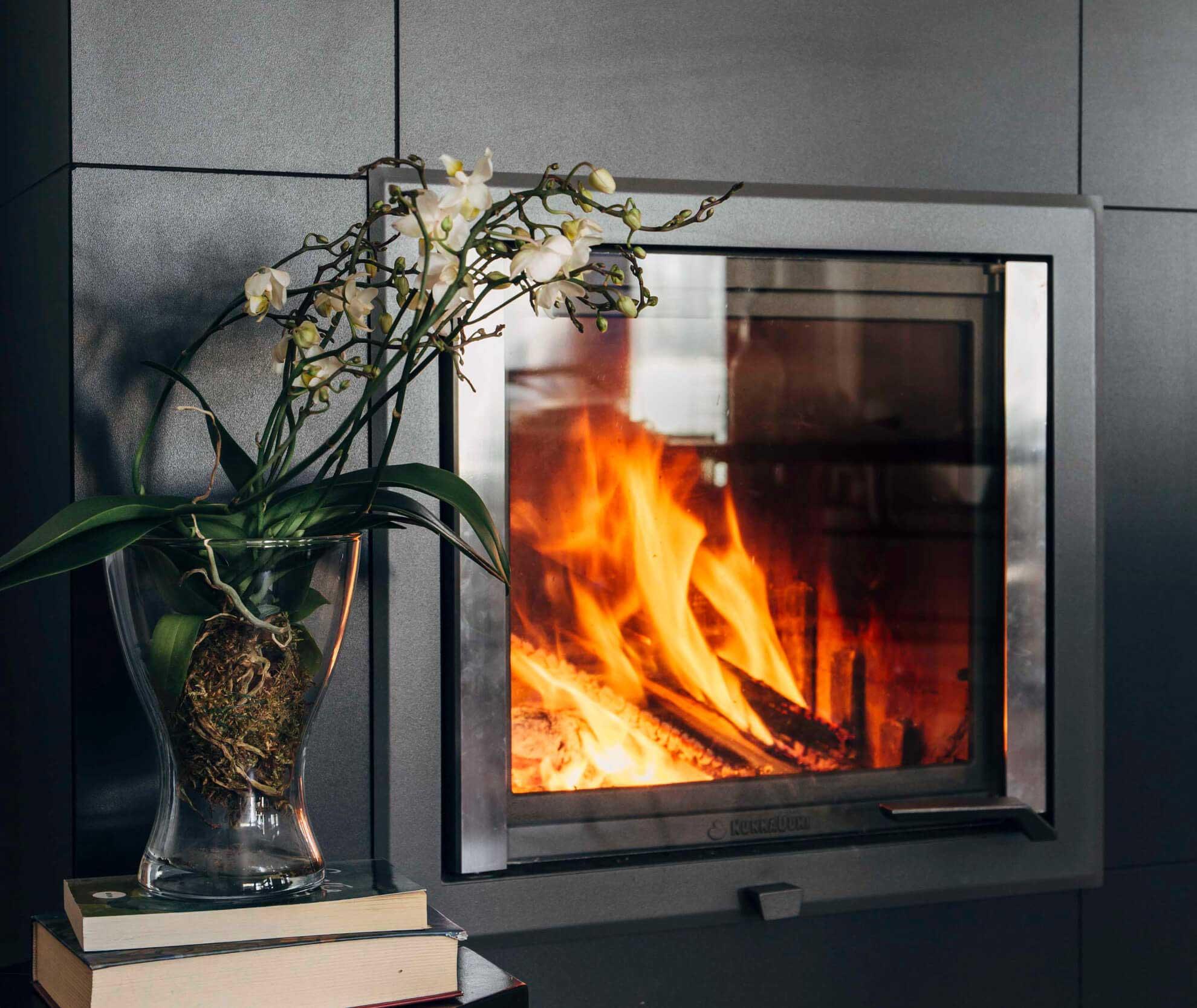 Ein neuer Speicherofen von NunnaUuni ist gut für die Umwelt. Das Goldene Feuer verbrennt die Holzscheite sauber und effektiv.